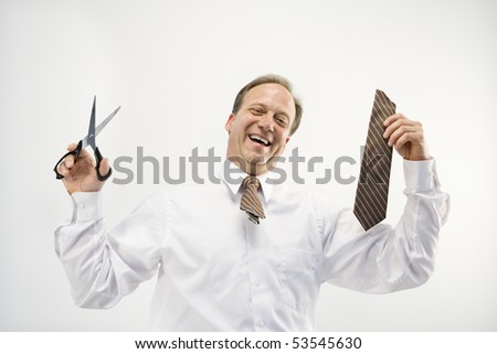 Caucasian middle aged businessman holding cut off necktie and scissors smiling. - stock photo