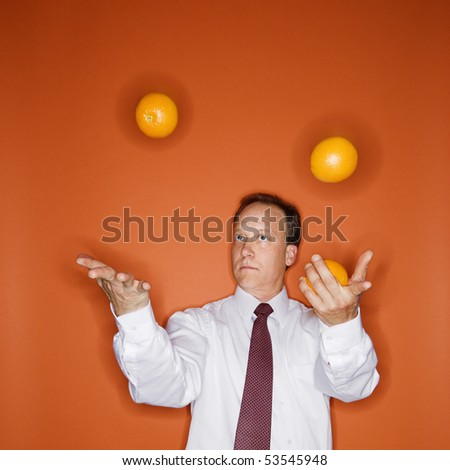 Caucasian middle aged businessman juggling oranges. - stock photo