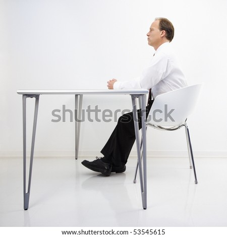 Caucasian middle aged businessman sitting at desk in office. - stock photo