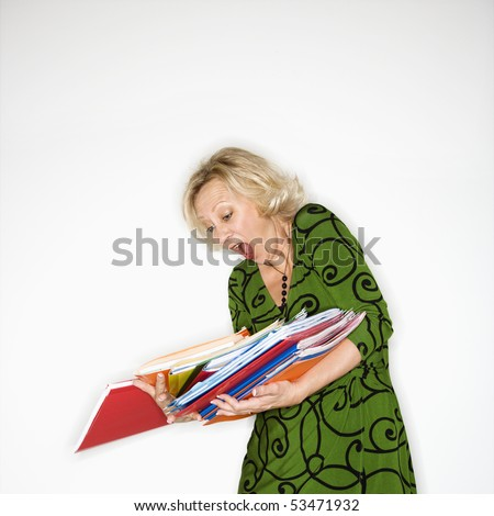 Caucasian middle aged businesswoman dropping stack of folders. - stock photo