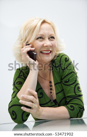 Caucasian middle aged businesswoman in office on cellphone smiling.