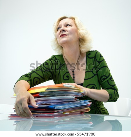 Caucasian middle aged businesswoman sitting at office desk with pile of folders. - stock photo