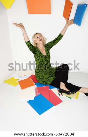 Caucasian middle aged businesswoman sitting on floor throwing stack of work folders into air.