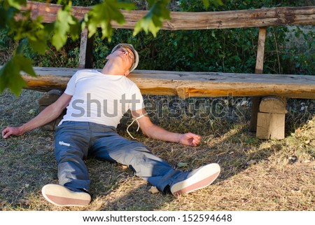 Caucasian middle-aged man lying down on the ground leaning his head on a bench feeling sick - stock photo