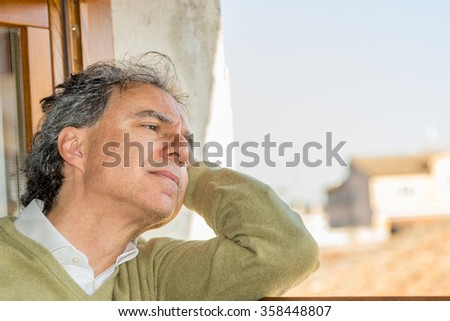 Caucasian middle-aged man with romantic and dreamy expression  with his head resting on one arm looks in the cityscape lost in thoughts
