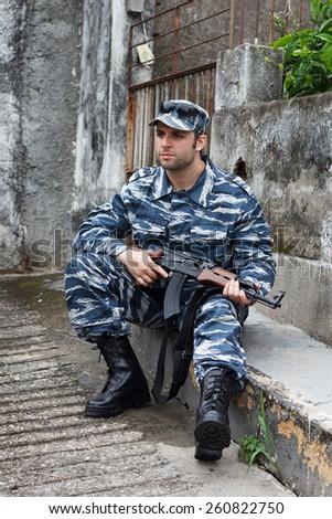 Caucasian military man in urban warfare sitting and holding machine gun . Selective focus - stock photo