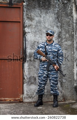Caucasian military man with black sunglasses in urban warfare holding automatic weapon near iron door  - stock photo
