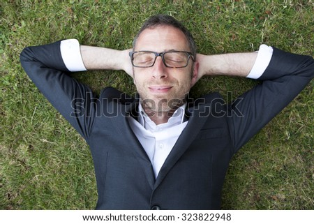 Caucasian modern businessman with grey suit and cool eyeglasses lying on grass sleeping and relaxing with hands behind head in city park enjoying time,overhead view,from above or high angle view - stock photo