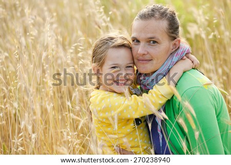 Caucasian mother and daughter hugging, smiling and sharing a tender bonding moment amongst meadow grass. Mothers day concept. Serenity and tranquility.  - stock photo