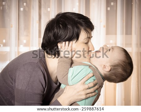 Caucasian mother and her baby boy playing together at home - stock photo