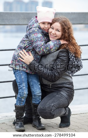 Caucasian mother embracing her daughter while walking outdoor, full-length portrait - stock photo