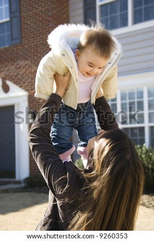 Caucasian mother holding up baby girl in front of house outside. - stock photo