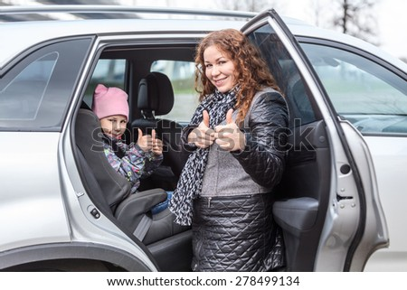 Caucasian mother showing thumbs up after fastening her daughter with seatbelt in car infant chair  - stock photo