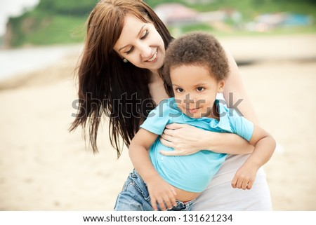 Caucasian mother with a son of an african descend having fun together outdoors. - stock photo