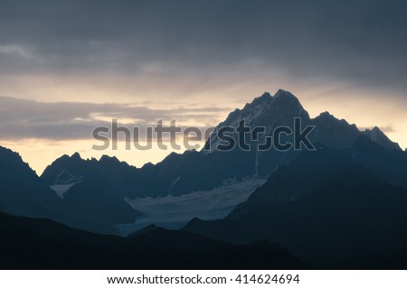 Caucasian mountains silhouettes at the rising sun. Warm yellow and orange abstract background. Svaneti, Georgia.