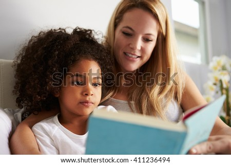 Caucasian mum and black daughter read book in bed, close-up - stock photo