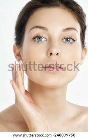 Caucasian natural woman touching her face.