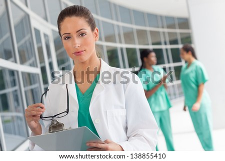 Caucasian nurse holding a clipboard in brightly lit exterior hospital environment in scrubs, white lab coat and holding glasses.  Two nurses in scrubs in the background.