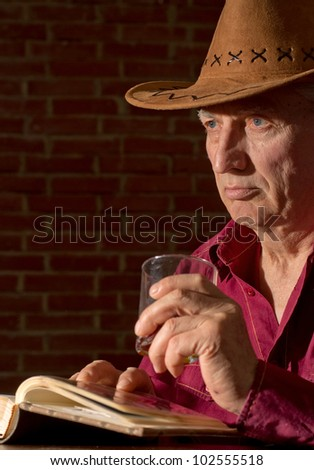 Caucasian old man with a nice glass sitting on a dark background - stock photo