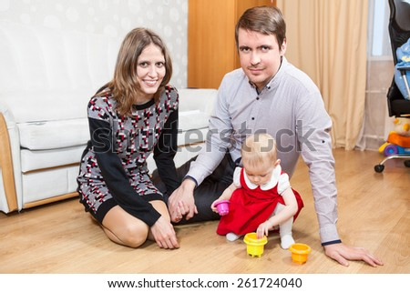 Caucasian parents looking at camera while baby girl playing on floor - stock photo