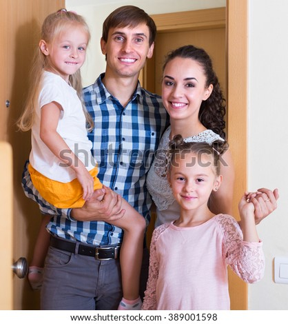 caucasian parents with kids standing at doorway of rented property