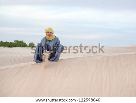 Caucasian person in protection eastern clothes pouring sand by hands on desert dune