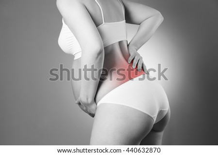 Caucasian pregnant woman in white lingerie with back pain on gray studio background - stock photo