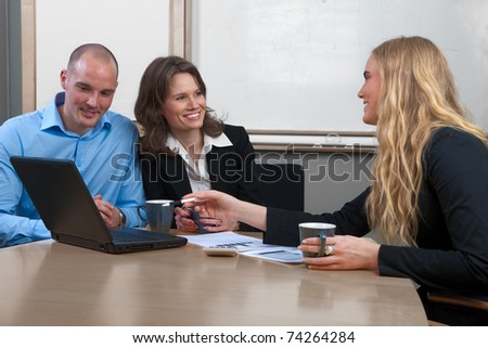 Caucasian professional businesswoman giving advice to caucasian couple in a conference room - stock photo