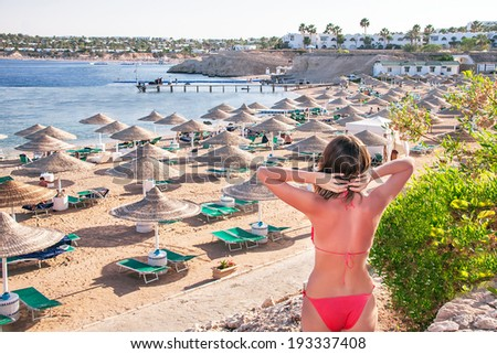 Caucasian resting girl is standing and enjoying view  of ocean and beach with parasoles. Happy relaxing beautiful young female model in red bikini. Summer vacation concept (Sharm El Sheikh, Egypt). - stock photo
