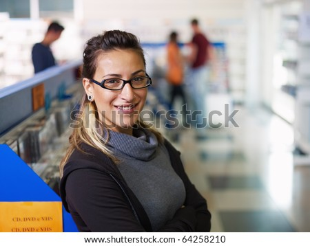 caucasian salesclerk looking at camera with arms folded in music shop, with customers in background. Horizontal shape, front view, waist up, copy space