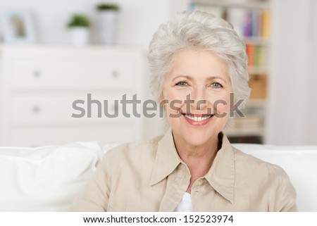 Caucasian senior beautiful woman enjoying the retirement home in her living room - stock photo