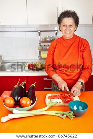 Caucasian senior woman in the kitchen with vegetables, preparing meal