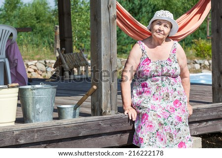 Caucasian senior woman resting near house in village - stock photo