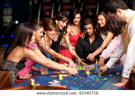 caucasian smiling adults and croupier placing bets - stock photo
