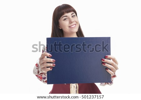 Caucasian Smiling Female Brunette Holding Blank Blue Plate for Text in Front. Focus on Board.  Isolated Against White.Horizontal Image Orientation