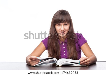 caucasian smiling girl sitting at desk with open book isolated on white