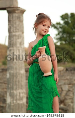Caucasian smiling little girl in a bright emerald green dress standing in the ruins of the ancient city of Pantikapaion in the role of the Greek goddess - stock photo