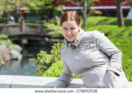 Caucasian smiling young woman in summer asian park. Half length portrait - stock photo