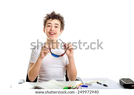 Caucasian smooth-skinned boy holding black plastic 3D Cinema eyeglasses with both hands while doing  homework - stock photo