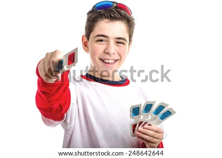 Caucasian smooth-skinned boy wears a pair of black 3D Cinema paper eyeglasses on his head with red and blue lenses and holds 4 white googles with left hand  while giving one with right hand - stock photo