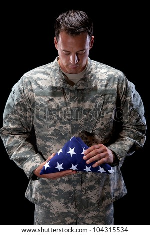 Caucasian soldier holds an American flag - stock photo
