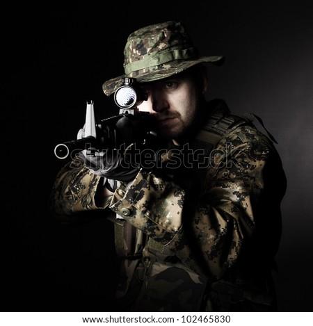 caucasian soldier with rifle dark background - stock photo