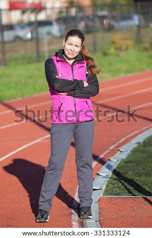 Caucasian sporty woman standing on the rubber lane of stadium - stock photo