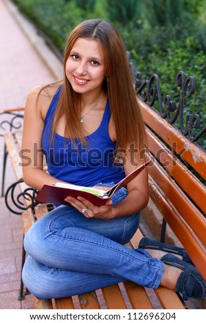 Caucasian student on the bench reading book - stock photo