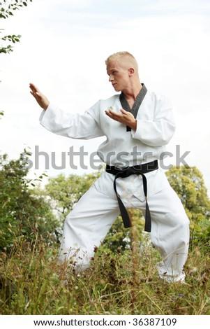 Caucasian Taekwondo fighter practicing outdoor - stock photo