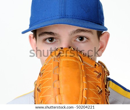 Caucasian teenage baseball pitcher looking over glove - stock photo