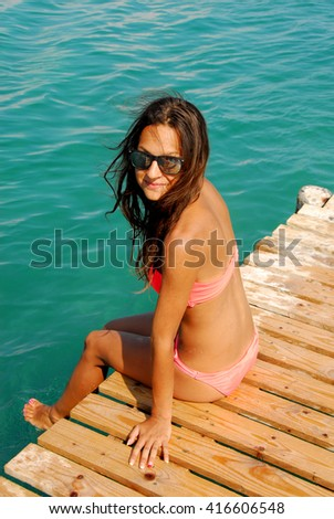 Caucasian teenage girl in swimsuit sitting on the wooden pier by blue Ionian sea, Greece