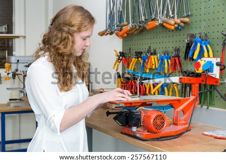 Caucasian teenage girl operating electric jigsaw in classroom - stock photo