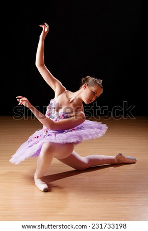 Caucasian teenage girl performing ballet in studio, with a wooden laminate floor and black background