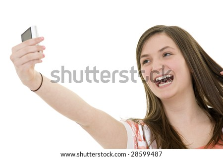 Caucasian teenager using a cell to take a pictue of herself on white background